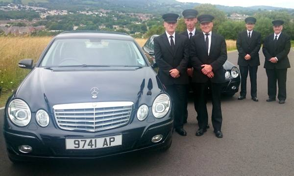 members of staff next to funeral car