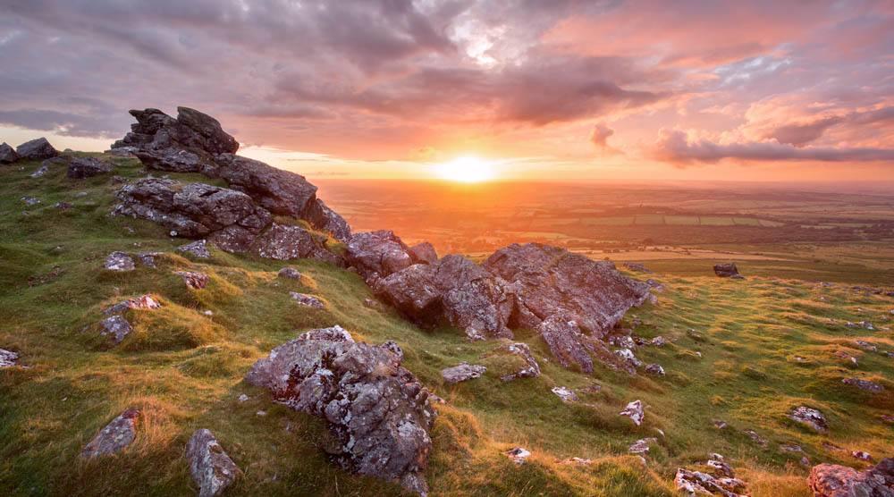 sun rising over rocks